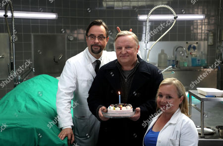 Stock Picture of Axel Prahl (C), who plays the role of police inspector Frank Thiel, German actor Jan Josef Liefers (L), who plays the role of Forensic Professor Dr. Karl-Friedrich Boerne and German actress Christine Urspruch (R), who plays the role of specialist in forensic medicine Dr. Silke Alberich Haller pose during a photo call in Cologne, Germany, 26 March 2018.