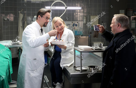 Stock Photo of Axel Prahl (R), who plays the role of police inspector Frank Thiel, German actor Jan Josef Liefers (L), who plays the role of Forensic Professor Dr. Karl-Friedrich Boerne and Geran actor ChrisTine Urspruch (C), who plays the role of specialist in forensic medicine Dr. Silke Alberich Haller pose during a phocall in Cologne, Germany, 26 March 2018.
