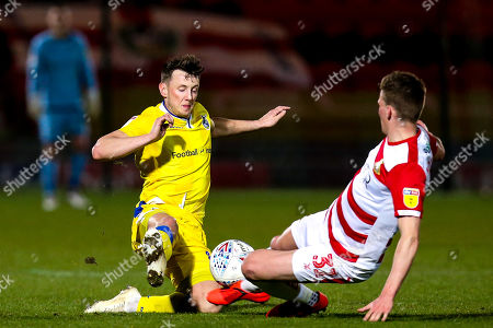 Ollie Clarke of Bristol Rovers tackles Paul Downing of Doncaster Rovers