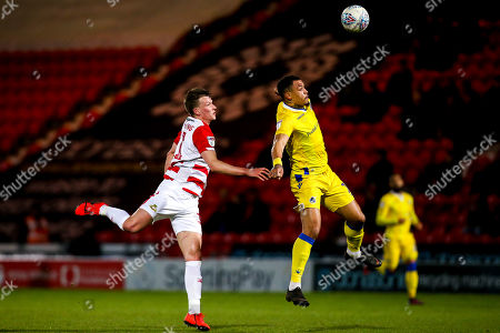 Jonson Clarke-Harris of Bristol Rovers beats Paul Downing of Doncaster Rovers to the ball