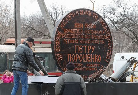 People transport a symbolic giant order to Ukrainian President Petro Poroshenko in the pro-Russian rebels controlled Gorlovka city of Donetsk area, Ukraine, 26 March 2019. The two meters diameter order named as 'Order of Judas' was made from debris of ammunition which were collected after shelling of Donetsk People's Republic (DPR) and will be displayed in the different cities of DPR.