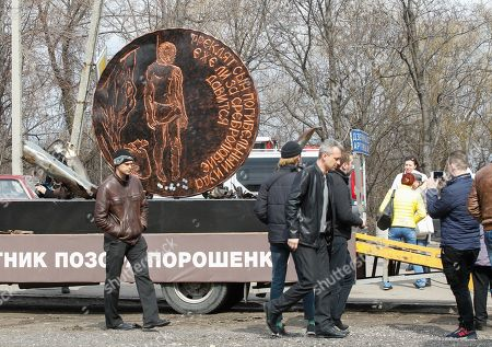 People walk past a symbolic giant order to Ukrainian President Petro Poroshenko in the pro-Russian rebels controlled Gorlovka city of Donetsk area, Ukraine, 26 March 2019. The two meters diameter order named as 'Order of Judas' was made from debris of ammunition which were collected after shelling of Donetsk People's Republic (DPR) and will be displayed in the different cities of DPR.
