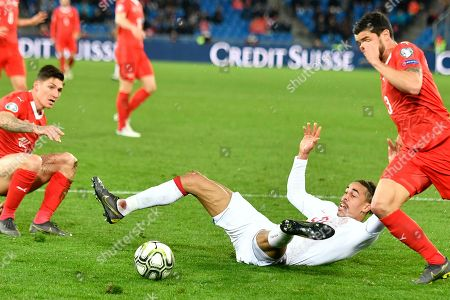 Switzerland's Steven Zuber (L), and Switzerland's Loris Benito (R), fights for the ball with Denmark's Yussuf Poulsen (C), during the UEFA Euro 2020 qualifying Group D soccer match between Switzerland and Denmark at the St. Jakob-Park stadium in Basel, Switzerland, 26 March 2019.