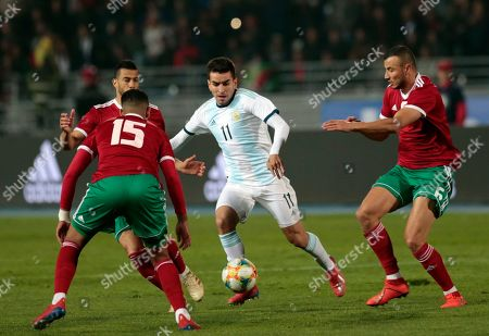 Argentina's Angel Correa, center, runs between Youssef Ait Bennasser, left, and Saiss Ghanem during an international friendly soccer match between Morocco and Argentina in Tangier, Morocco