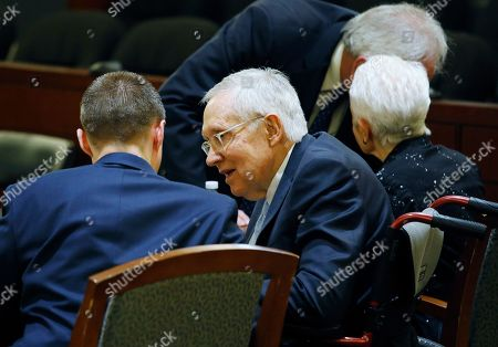 Former U.S. Sen. Harry Reid, second from left, sits in court, in Las Vegas. A jury in Nevada heard opening arguments Tuesday in Reid's lawsuit against the maker of a flexible exercise band that he says slipped from his hand while he used it in January 2015, causing him to fall and suffer lasting injuries including blindness in one eye