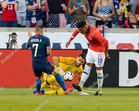Chile goalkeeper Brayan CortŽs (12) looks on as defender Gonzalo Jara (18) battles the ball from USA forward Paul Arriola (7) during the second half of the international friendly match between USA and Chile at BBVA Compass Stadium in Houston, Texas The final ends in a tie 1-1