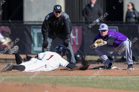 Harvard's Ben Skinner, left, dives safely back to first base as Holly Cross' Evan Blum catches the pick-off attempt during an NCAA college baseball game, in Boston