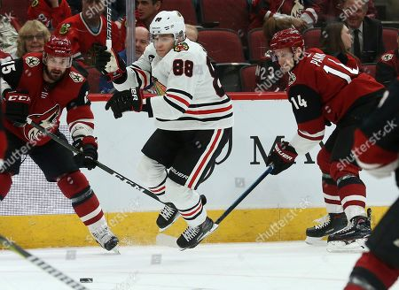 Chicago Blackhawks right wing Patrick Kane (88) gets tripped up by Arizona Coyotes right wing Richard Panik (14) as Coyotes center Brad Richardson (15) looks for the puck during the first period of an NHL hockey game, in Glendale, Ariz