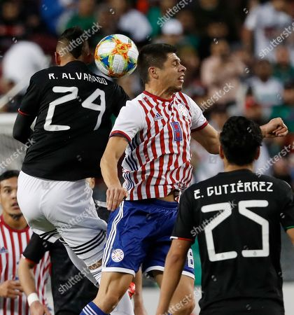 Roberto Alvarado of Mexico (L) and Rodrigo Rojas of Paraguay (C) in action during the first half of the international friendly soccer match between Mexico and Paraguay at the Levi's Stadium in Santa Clara, California, USA, 26 March 2019.