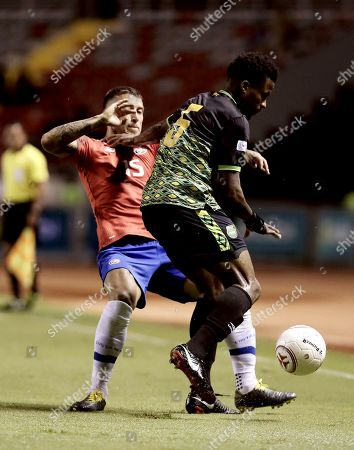 Francisco Calvo (L) of Costa Rica vies for the ball against Alvas Powell (R) of Jamaica during a international friendly soccer match between Costa Rica and Jamaica, in San Jose, Costa Rica, 26 March 2019.