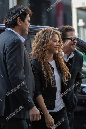 Colombian singers Shakira, center, and Carlos Vives, right, arrive at court in Madrid, Spain