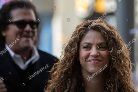 Colombian singers Shakira, right, and Carlos Vives, background, arrive at court in Madrid, Spain