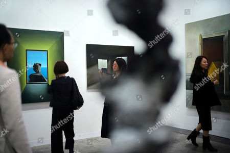 People walk past an artwork created by Chinese artist Zhang Ying Nan at Art Basel in Hong Kong . Art Basel, one of the world's most prestigious modern and contemporary art exhibitions, is returning to Hong Kong in its seventh edition. The prestige art fair is hosting 242 galleries from 35 countries and territories