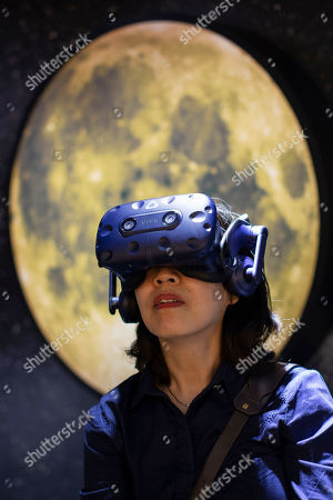 A visitor tries virtual reality goggles to experience a virtual reality work entitled 'To The Moon' by artists Laurie Anderson and Huang Hsin Chien at Art Basel in Hong Kong, China, 27 March 2019. Art Basel, Asia's biggest contemporary art fair, open to the general public from 29 to 31 March 2019.