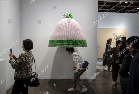 Stock Picture of A visitor walks under an art piece by Erwin Wurm entitled 'Title to be determined (Austrian mountain cap)' displayed at the Art Basel in Hong Kong, China, 27 March 2019. Art Basel, Asia's biggest contemporary art fair, open to the general public from 29 to 31 March 2019.
