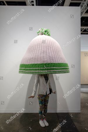 A visitor stands under an art piece by Erwin Wurm entitled 'Title to be determined (Austrian mountain cap)' displayed at the Art Basel in Hong Kong, China, 27 March 2019. Art Basel, Asia's biggest contemporary art fair, open to the general public from 29 to 31 March 2019.
