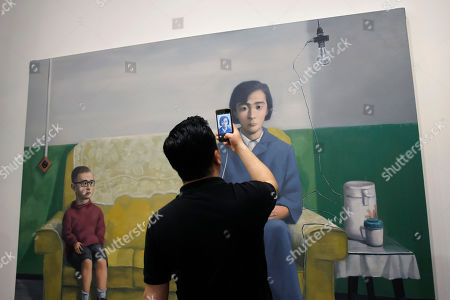 "A visitor takes a picture of the painting ""My Mother"" created by Chinese artist Zhang Xiaogang at Art Basel in Hong Kong . Art Basel, one of the world's most prestigious modern and contemporary art exhibitions, is returning to Hong Kong in its seventh edition. The prestige art fair is hosting 242 galleries from 35 countries and territories"