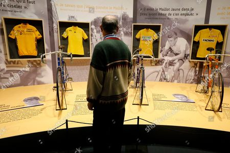 Stock Image of A visitor looks at the yellow jersey of Spanish rider Miguel Indurain (L), French riders Bernard Hinault (2-L), Jacques Anquetil (2-R) and Belgian rider Eddy Merckx (R) on display during the exhibition '100 years Yellow Jersey' at the National Sport Museum in Nice, France, 27 March 2019. The exhibition runs from 17 March to 29 September 2019.