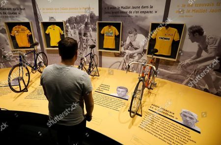 A visitor looks at the yellow jersey of Spanish rider Miguel Indurain (L), French riders Bernard Hinault (2-L), Jacques Anquetil (2-R) and Belgian rider Eddy Merckx (R) on display during the exhibition '100 years Yellow Jersey' at the National Sport Museum in Nice, France, 27 March 2019. The exhibition runs from 17 March to 29 September 2019.