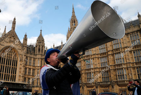 A pro EU protestor shouts through a megaphone at the Houses of Parliament in London, . British lawmakers were preparing to vote Wednesday on alternatives for leaving the European Union as they seek to end an impasse following the overwhelming defeat of the deal negotiated by Prime Minister Theresa May