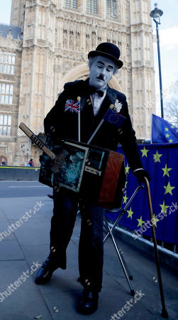 A protestor dressed as comedic actor Charlie Chaplin, demonstrates in front of the Houses of Parliament in London, . British lawmakers were preparing to vote Wednesday on alternatives for leaving the European Union as they seek to end a political impasse following the overwhelming defeat of the deal negotiated by Prime Minister Theresa May