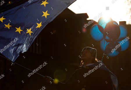 A Pro EU protestor demonstrates in front of the Houses of Parliament in London, . British lawmakers were preparing to vote Wednesday on alternatives for leaving the European Union as they seek to end an impasse following the overwhelming defeat of the deal negotiated by Prime Minister Theresa May