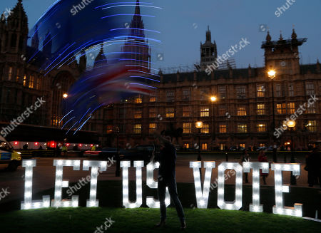 "1.2 metre-tall illuminated sign reading ""LET US VOTE"" is set up outside Parliament by the public and civic organisation Avaaz in London, . British lawmakers were preparing to vote Wednesday on alternatives for leaving the European Union as they seek to end an impasse following the overwhelming defeat of the Brexit deal negotiated by Prime Minister Theresa May"