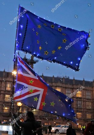 A protestor waves flags outside of the Houses of Parliament in London, . British lawmakers were preparing to vote Wednesday on alternatives for leaving the European Union as they seek to end an impasse following the overwhelming defeat of the Brexit deal negotiated by Prime Minister Theresa May