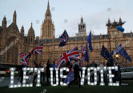 "1.2 metre-tall illuminated letters declaring ""LET US VOTE"" are set up outside Parliament by the public and civic organisation Avaaz in London, . British lawmakers were preparing to vote Wednesday on alternatives for leaving the European Union as they seek to end an impasse following the overwhelming defeat of the deal negotiated by Prime Minister Theresa May"