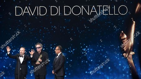 Tim Burton (C) with Italian film director and actor Roberto Benigni (L) and Italian presenter Carlo Conti (R) on stage in the occasion of the 64th edition of the David di Donatello Awards in Rome, Italy, 27 March 2019. The David di Donatello award is a film prize presented annually to honor the best of Italian and foreign motion picture productions.