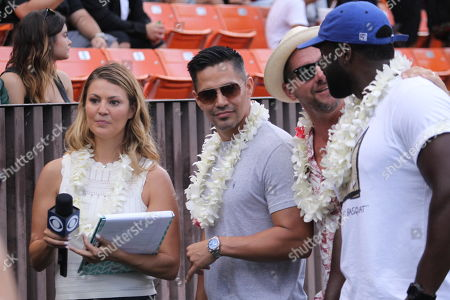 Stock Image of Amanda Balionis talks with the new Magnum P.I. actor Jay Hernandez and co-stars Zachary Knighton (Rick) and Stephen Hill (T.C.) during a game between the Hawaii Rainbow Warriors and the Navy Midshipmen at Aloha Stadium in Honolulu, HI - Michael Sullivan/CSM