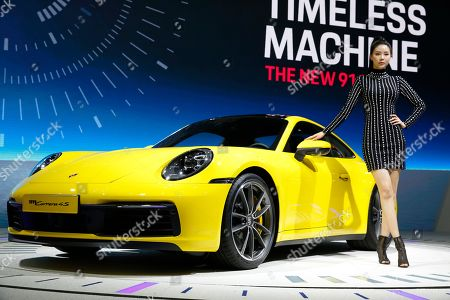A model poses next to the Porsche 911 Carrera 4 S during the 2019 Seoul Motor