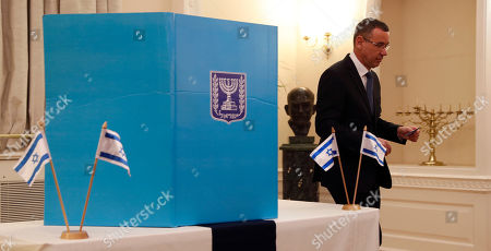Mark Regev, the Israeli Ambassador to Britain holds his voting ballot as he prepares to vote, at the Israeli Embassy in London, . Some 5000, Israeli citizens worldwide who work for the government or official industries are allowed to vote abroad, other citizens must vote by being in Israel