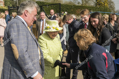 Queen Elizabeth II greets staff accompanied by trainer Paul Nicholls (L) during a visit to Manor Farm Stables in Ditcheat