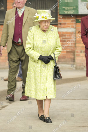Stock Image of Queen Elizabeth II greets trainers and staff during a visit to Manor Farm Stables in Ditcheat