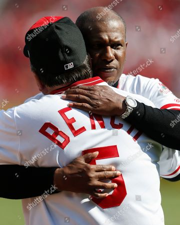 Eric Davis, Johnny Bench. Former Cincinnati Reds player Eric Davis, right, hugs Johnny Bench, left, after throwing out the ceremonial first pitch before an opening day baseball game against the Pittsburgh Pirates, in Cincinnati