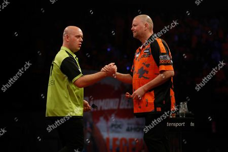 Dutch dart players Michael van Gerwen (L) and Raymond van Barneveld greet each other prior to their match during the Premier League Darts in Rotterdam, Thursday 28 March 2019. 'Barney' lost his very last Premier League match with 7-1.