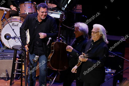"""Vince Gill, left, laughs after performing with Marty Stuart, center, and Ricky Skaggs during a television taping for the new Ken Burns documentary """"Country Music"""" at the Ryman Auditorium, in Nashville, Tenn. The PBS film is set to air in September"""