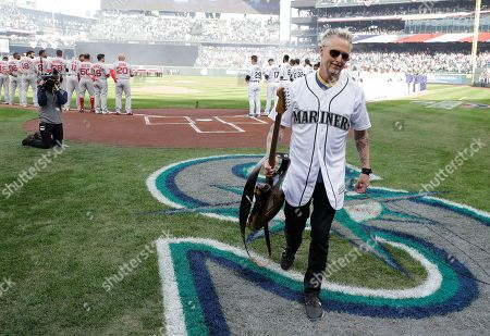 Stock Picture of Pearl Jam guitarist Mike McCready carries his guitar after performing the national anthem before a baseball game between the Seattle Mariners and the Boston Red Sox, in Seattle