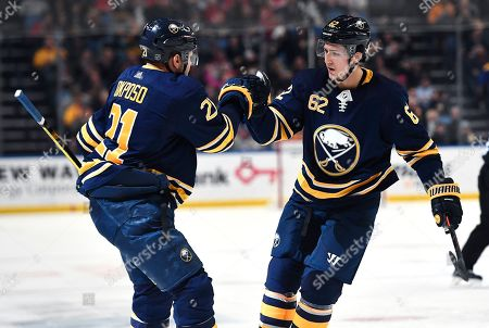 Buffalo Sabres defenseman Brandon Montour (62) congratulates right wing Kyle Okposo (21) on his goal during the second period of an NHL hockey game against the Detroit Red Wings in Buffalo, N.Y