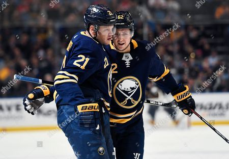 Buffalo Sabres defenseman Brandon Montour, right, congratulates right wing Kyle Okposo on his goal during the second period of the team's NHL hockey game against the Detroit Red Wings in Buffalo, N.Y