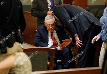 Former U.S. Sen. Harry Reid, center, sits in a wheelchair in court, in Las Vegas. Reid testified in his negligence lawsuit against the maker of an exercise device
