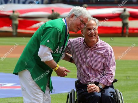 Former Arlington mayor Richard Greene poses for a photo with Texas Governor Greg Abbott after Abbott threw out the ceremonial first pitch at the opening day baseball game between the Chicago Cubs and Texas Rangers in Arlington, Texas