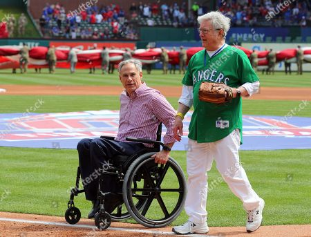 Texas Governor Greg Abbott and former Arlington mayor Richard Greene walk off the field with after Abbott threw out the ceremonial first pitch at the opening day baseball game between the Chicago Cubs and Texas Rangers in Arlington, Texas