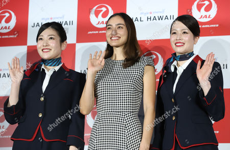 Japanese-American model Jun Hasegawa (C) smiles with Japan Airlines (JAL) cabin attendants as she attends an event of JAL's tourism promotion to Hawaii with Hilton Grand Vacations