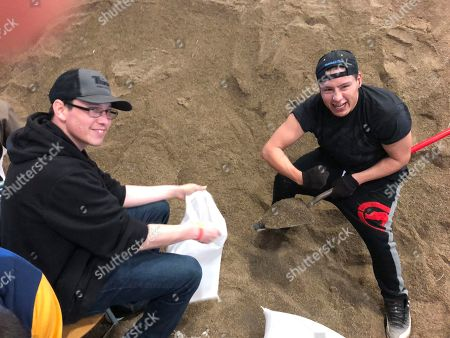 Daniel Barrett and Devan Keezer. Daniel Barrett, right, of Red Lake, Minn., strikes a pose while he and Devan Keezer, of White Earth, Minn., fill sandbags in Fargo, N.D. Volunteers from around the region are coming to help the city fill bags to protect itself against possible major flooding from spring runoff in mid-April. The city wants to fill 1 million sandbags within the next two weeks