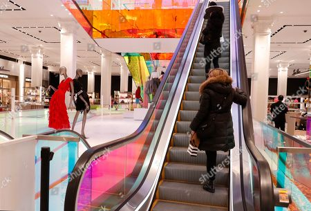 Stock Image of Shoppers ride the escalator at Saks Fifth Avenue's flagship midtown Manhattan store, in New York. Company insider Marc Metrick has overseen what he calls a $250 million redevelopment which he hopes will reinvent the department store experience to bring theater to luxury shopping at a time when shoppers can buy their designer handbags online