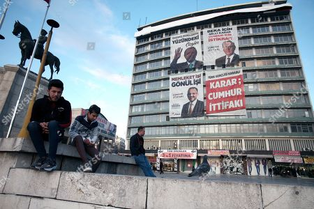 Teenagers sit next to a statue depicting Turkey's War of Independence in old part of Turkish capital, Ankara, Turkey, . A poster with images of Turkey's President Recep Tayyip Erdogan, top left, Devlet Bahceli, leader of the opposition Nationalist Movement Party, MHP, top right, and Mehmet Ozhaseki, the mayoral candidate for Ankara of Erdogan's ruling Justice and Development Party, AKP, and MHP is in the background, ahead of local elections scheduled for March 31, 2019