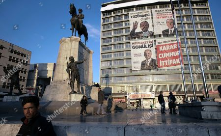 An unemployed man stands next to a statue depicting Turkey's War of Independence in old part of Turkish capital, Ankara, Turkey, . A poster with images of Turkey's President Recep Tayyip Erdogan, top left, Devlet Bahceli, leader of the opposition Nationalist Movement Party, MHP, top right, and Mehmet Ozhaseki, the mayoral candidate for Ankara of Erdogan's ruling Justice and Development Party, AKP, and MHP is in the background, ahead of local elections scheduled for March 31, 2019