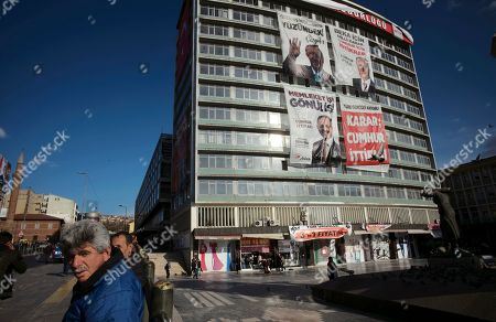 Unemployed men stand next to a statue depicting Turkey's War of Independence in old part of Turkish capital, Ankara, Turkey, . A poster with images of Turkey's President Recep Tayyip Erdogan, top left, Devlet Bahceli, leader of the opposition Nationalist Movement Party, MHP, top right, and Mehmet Ozhaseki, the mayoral candidate for Ankara of Erdogan's ruling Justice and Development Party, AKP, and MHP is in the background, ahead of local elections scheduled for March 31, 2019